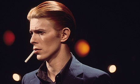 David Bowie smoking a cigarette with slicked back hair.jpg