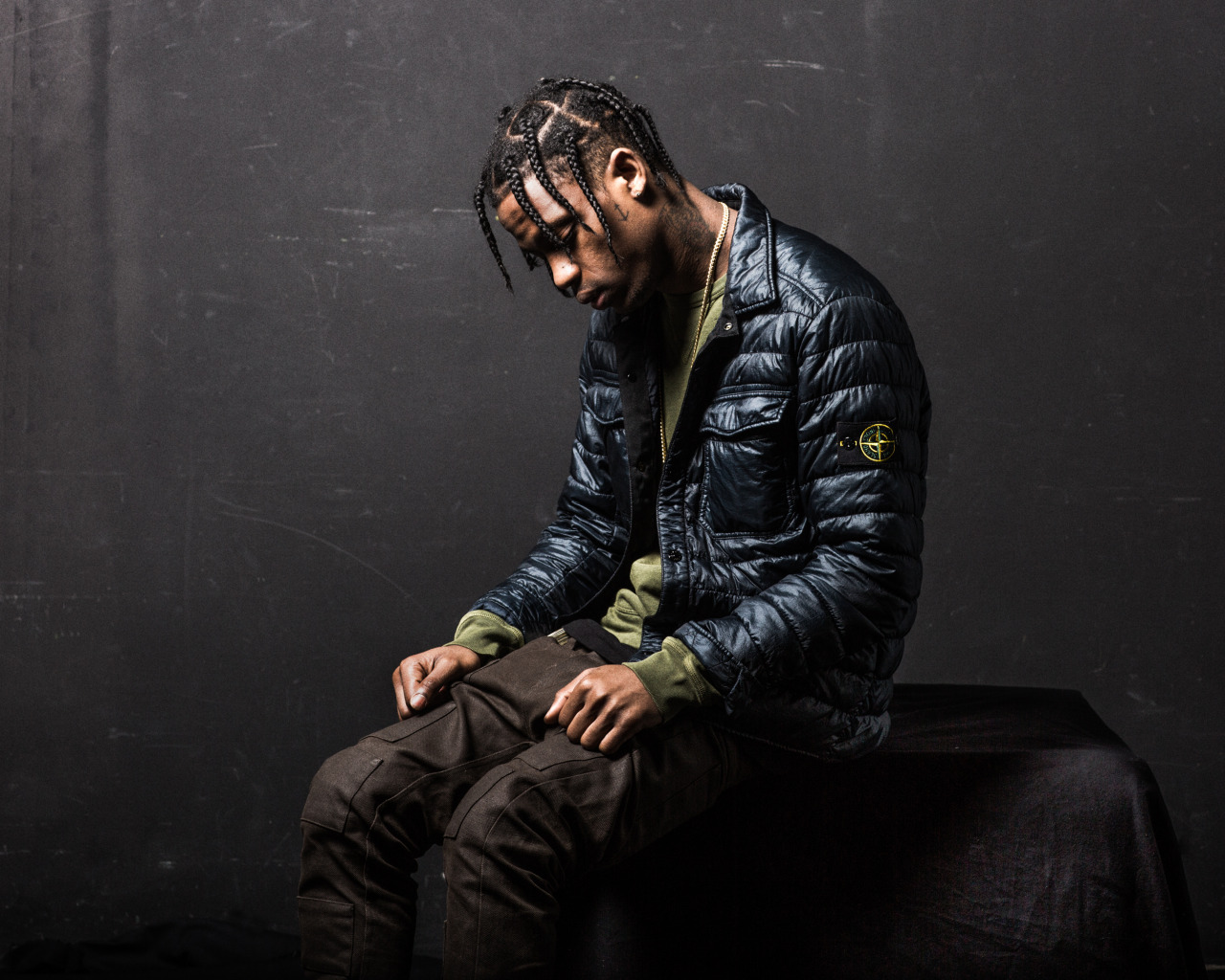 Travi$ Scott looking hot as he sits down in a dark area while wearing a puffer jacket.jpg