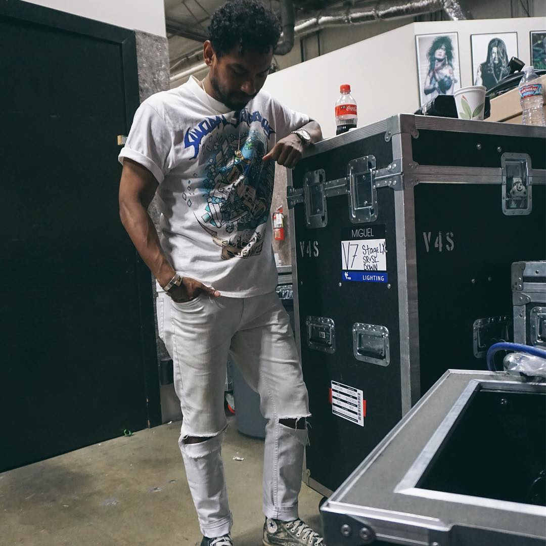 Miguel wearing a white tee and white ripped jeans looking gorgeous backstage on the Sia tour.jpg