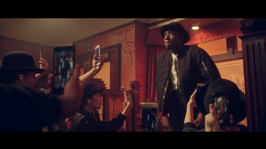white people looking through their cell phone at the bar in Will.I.Am's Fiyah video.jpg