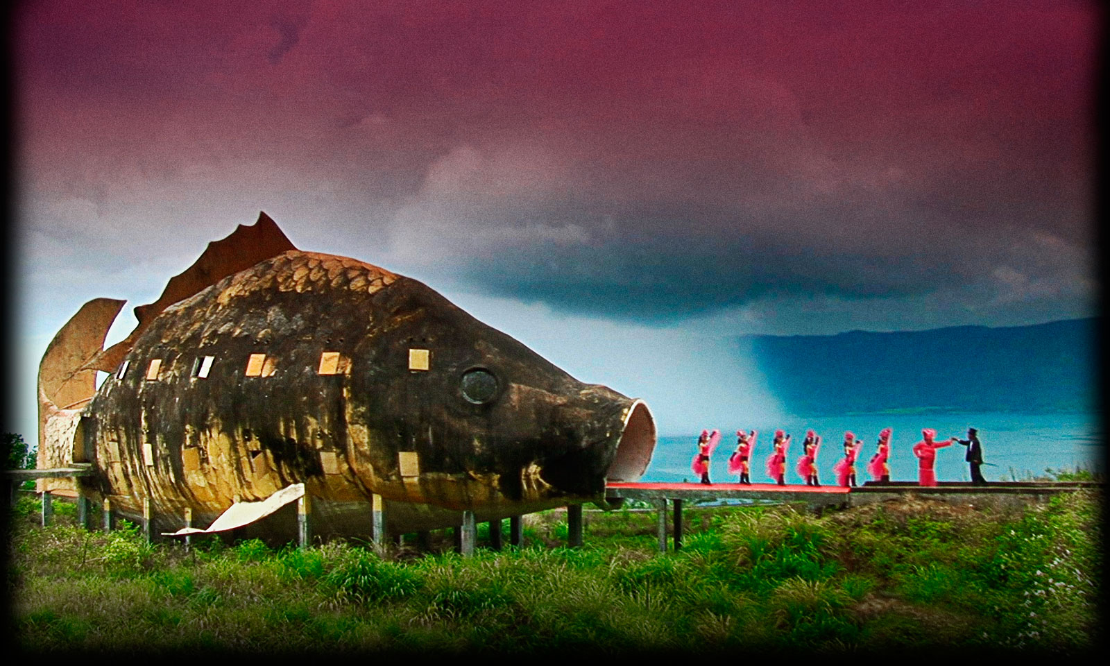 Girls in pink dresses dance into the mouth of a giant fish, a scene leading up to the final fictionalized and self-created homage to the genocidal killers.