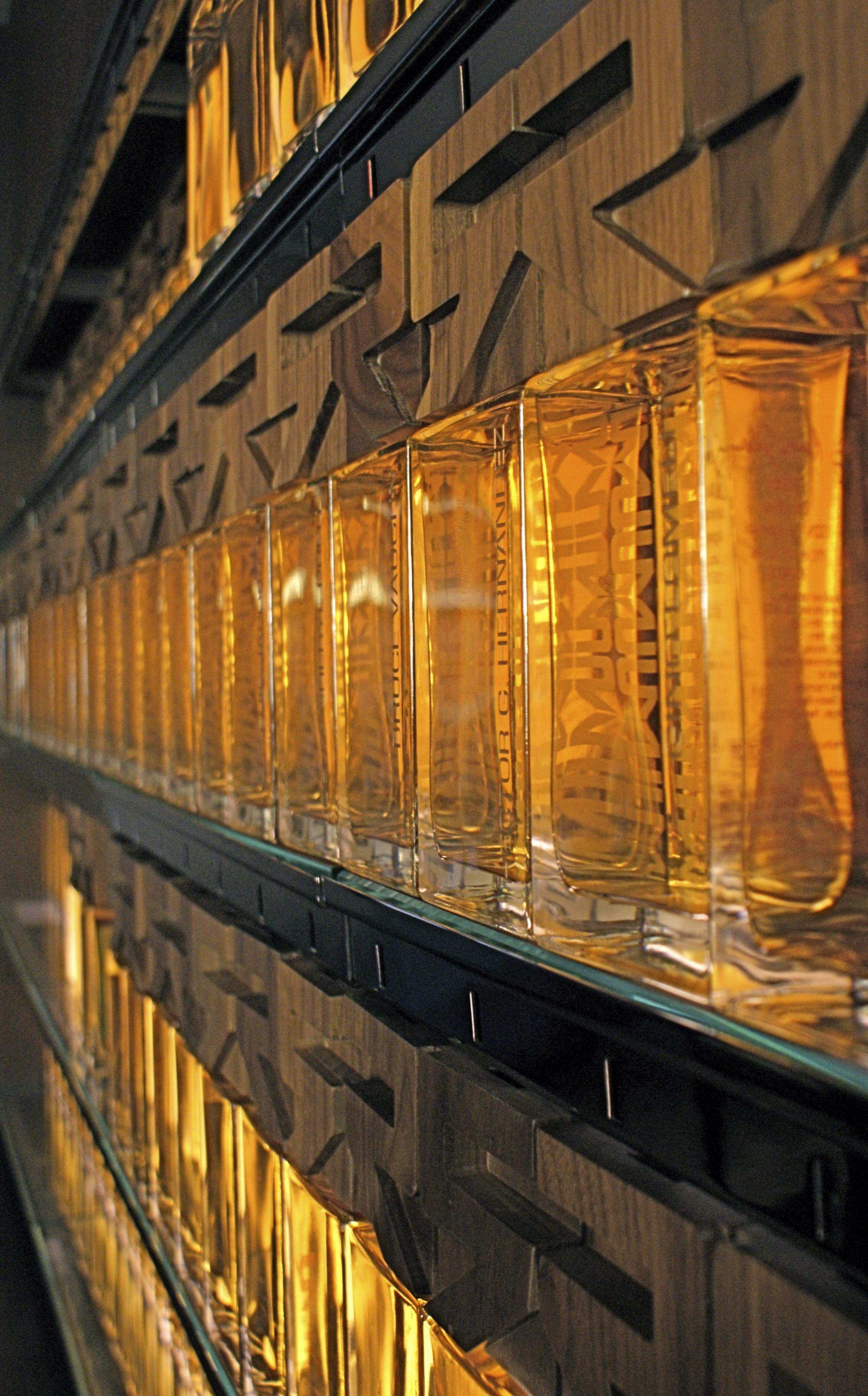"""A matching signature Tequila Library also is part of the package. Seen here at Rivera as """"bricks"""" in the liquid """"wall"""", each Walnut Cap accessed by a member's gold key."""