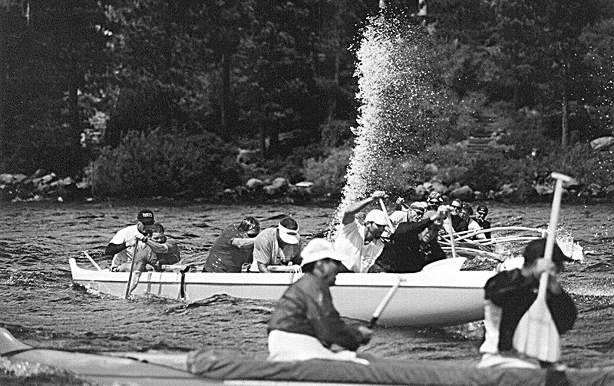 Seat 3 bailing . . . NOTE SEAT 1 HAS COME OVER / OR REMAINED ON THE LEFT AFTER THE 'HUT' WAS CALLED, TO PROTECT THE AMA, however, seat 1 has minimal control over canoe stability, which is more greatly offset by the middle seats (and the steerer!). If you travel to an event and paddle an unfamiliar canoe, be sure to check where the water 'pools' so as you know which seat will need to be bailing most. This water plume, indicates good bailing technique and by the looks of it, they are paddling downwind.