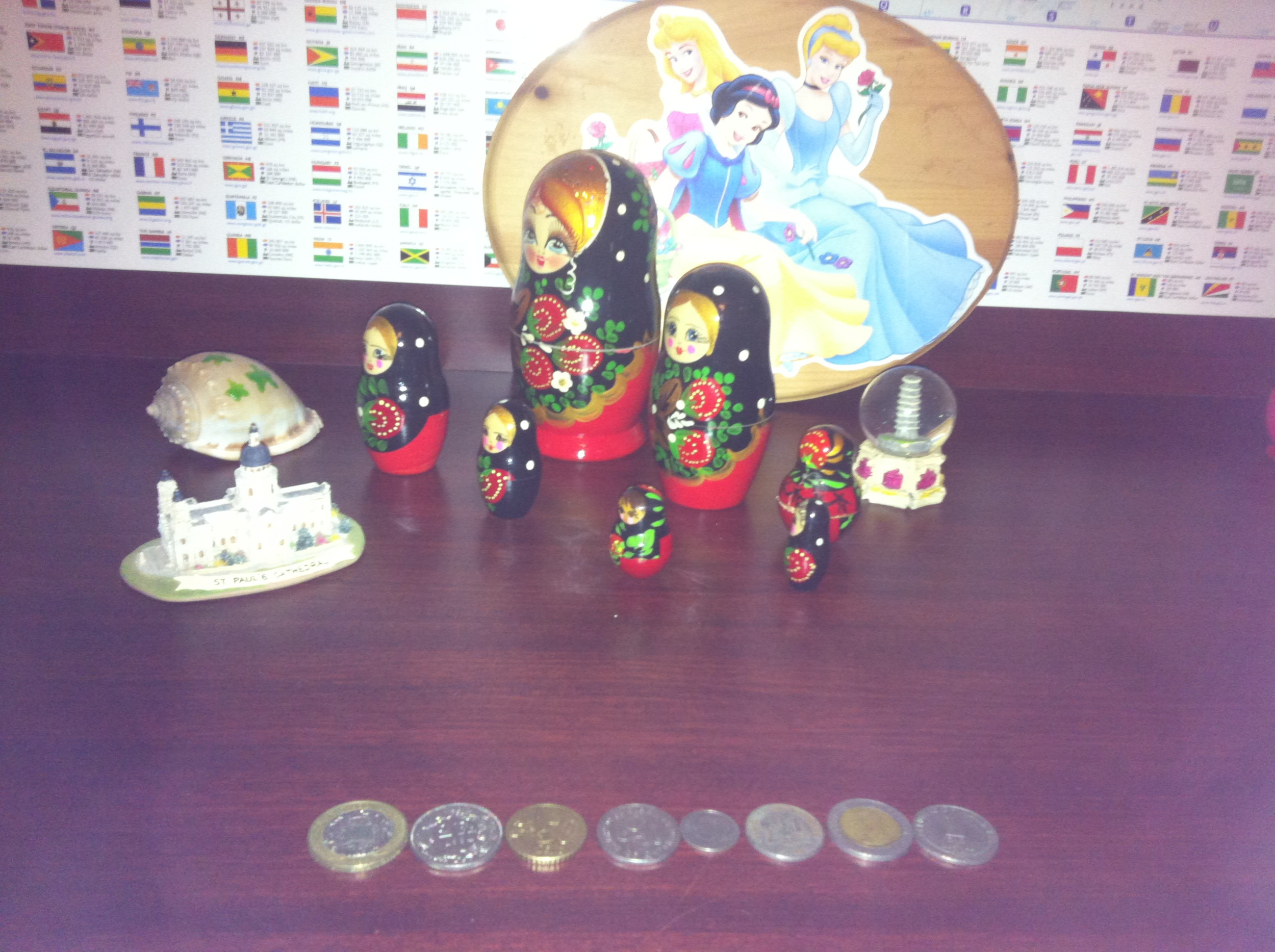Kiddo's world coins laid out by world flag map, Disney princesses, Philippine conch, Russian matryoshka dolls, a Leaning Tower of Pisa globe and a mini St. Paul's Cathedral.