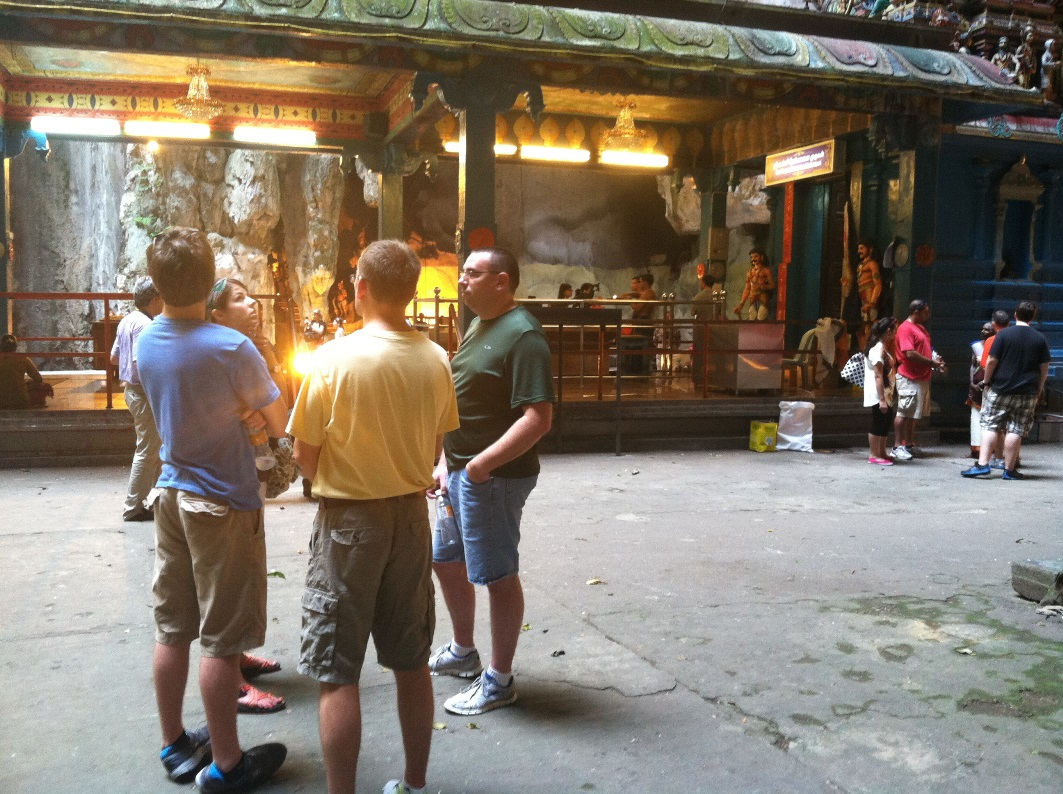 Praying as members of our team share Christ with one of the shrine workers