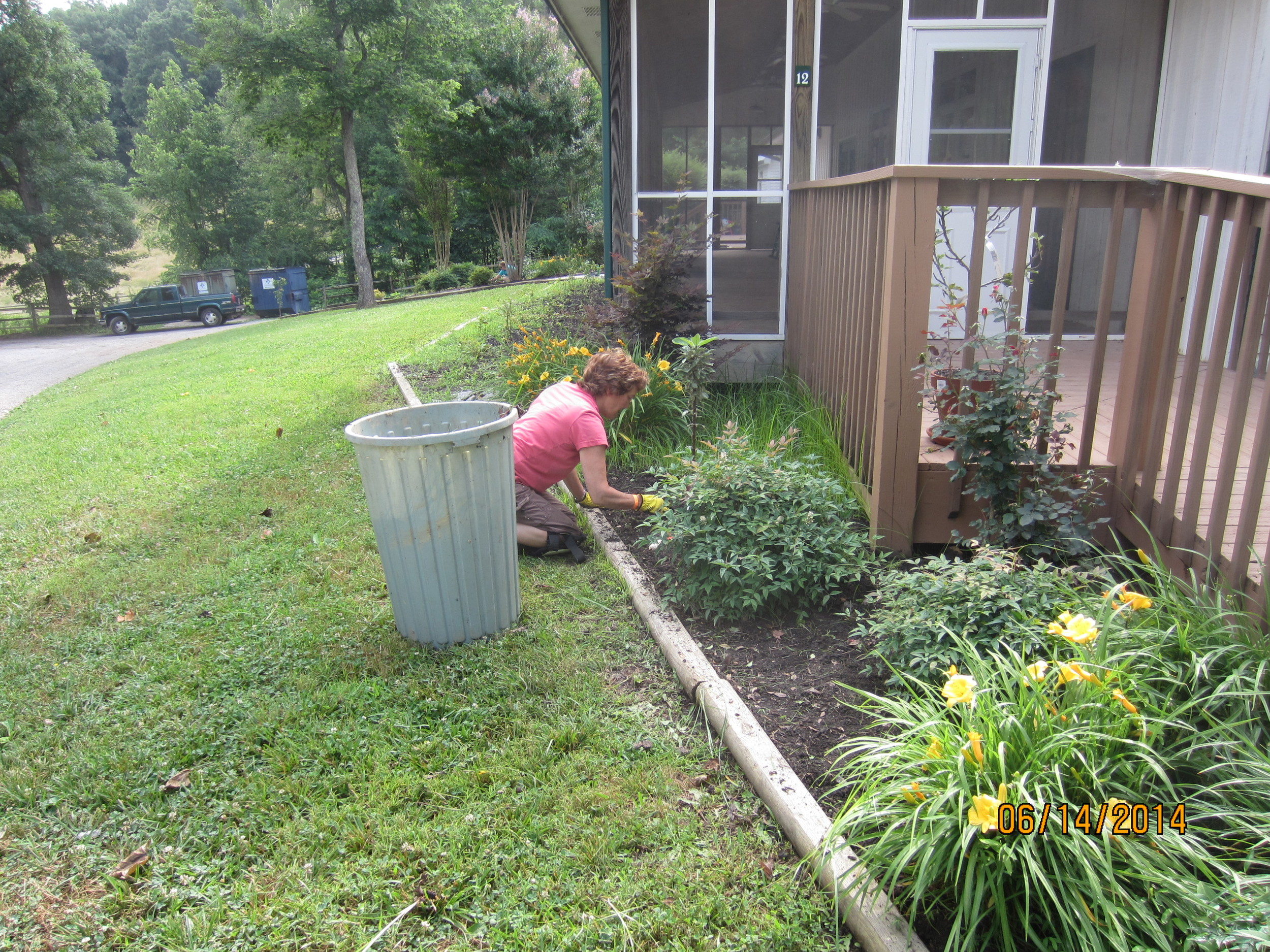 Nanci Scott continues with weeding at the Dining Hall, in preparation of spreading new mulch in the flower beds.