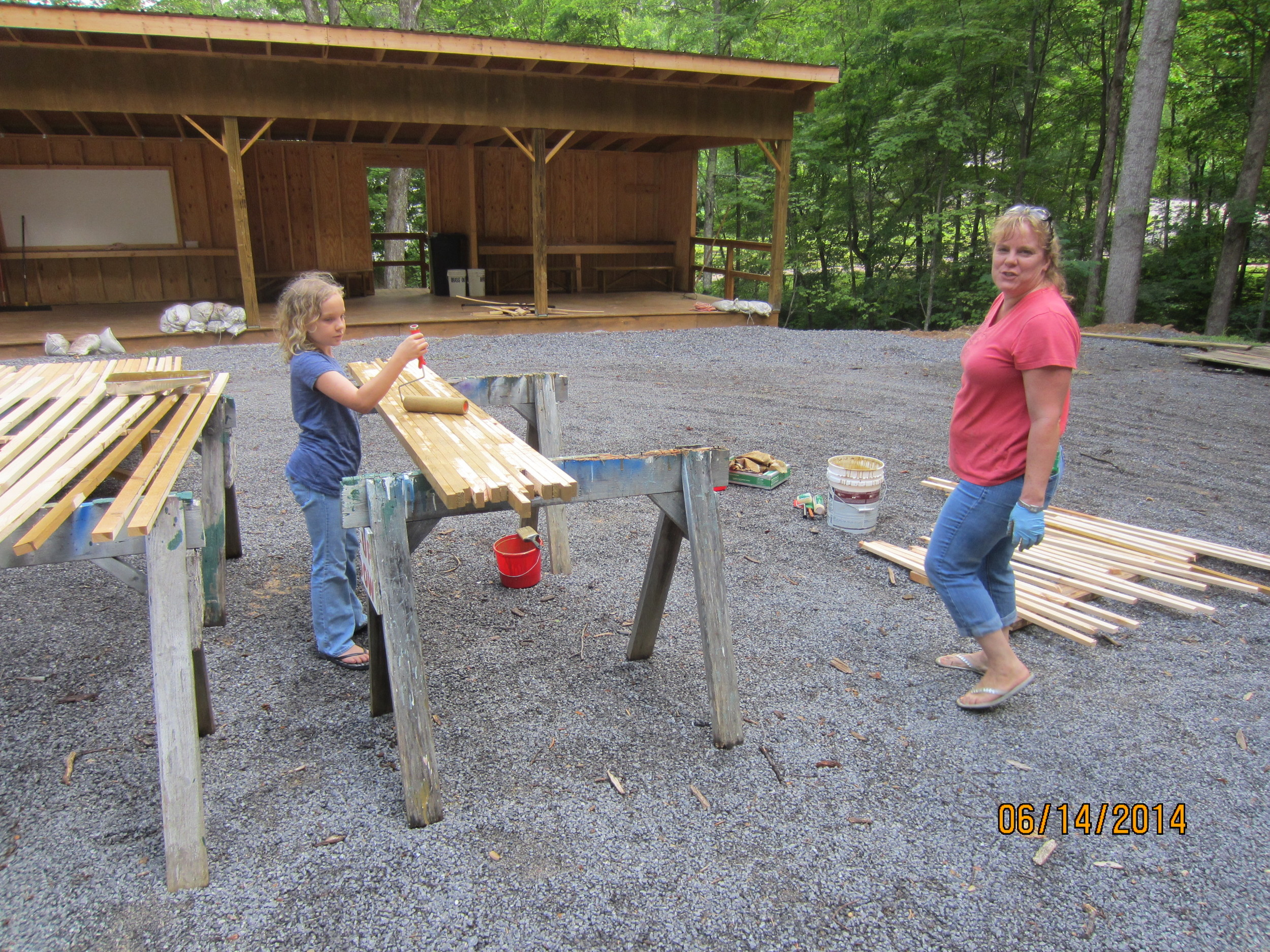 Jorja and Heide Reid finish painting the lumber needed at the new Firing Range that got wet on Friday, but is now dry enough to paint.