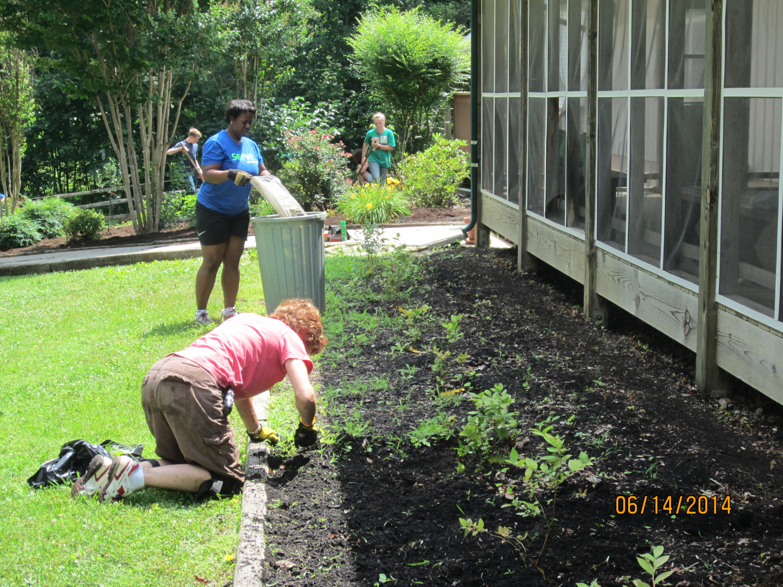 Nanci Scott, Demetria Utley, Zach and Allie Reid continue to prepare the Dining Hall beds for mulching.