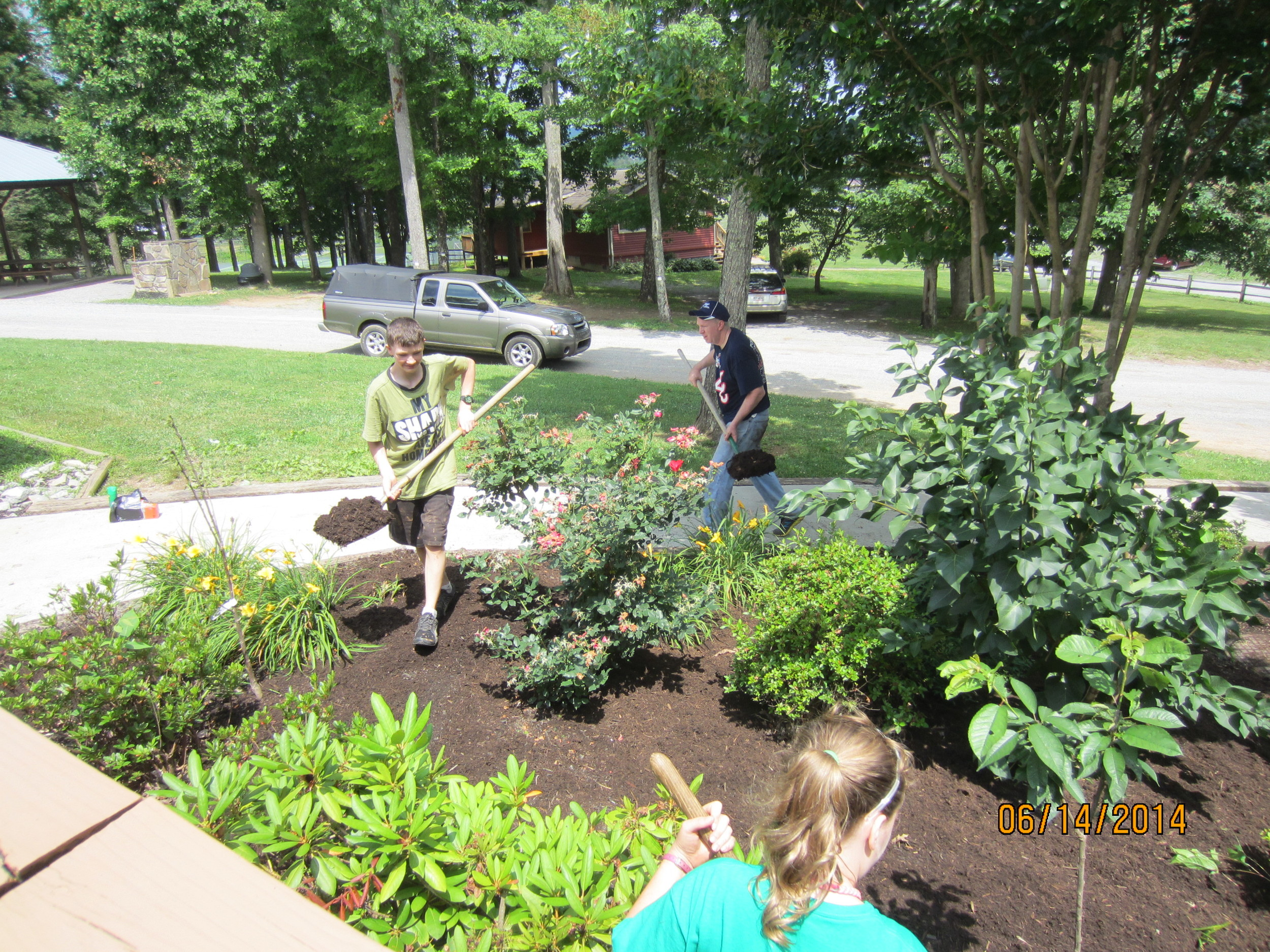 Oleg, Allie and Jonathan Reid mulching the beds around the Dining Hall.