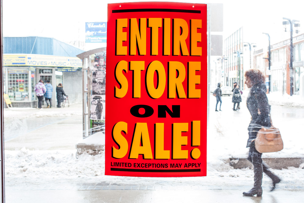 People on the street walk by signs advertising blowout sales.