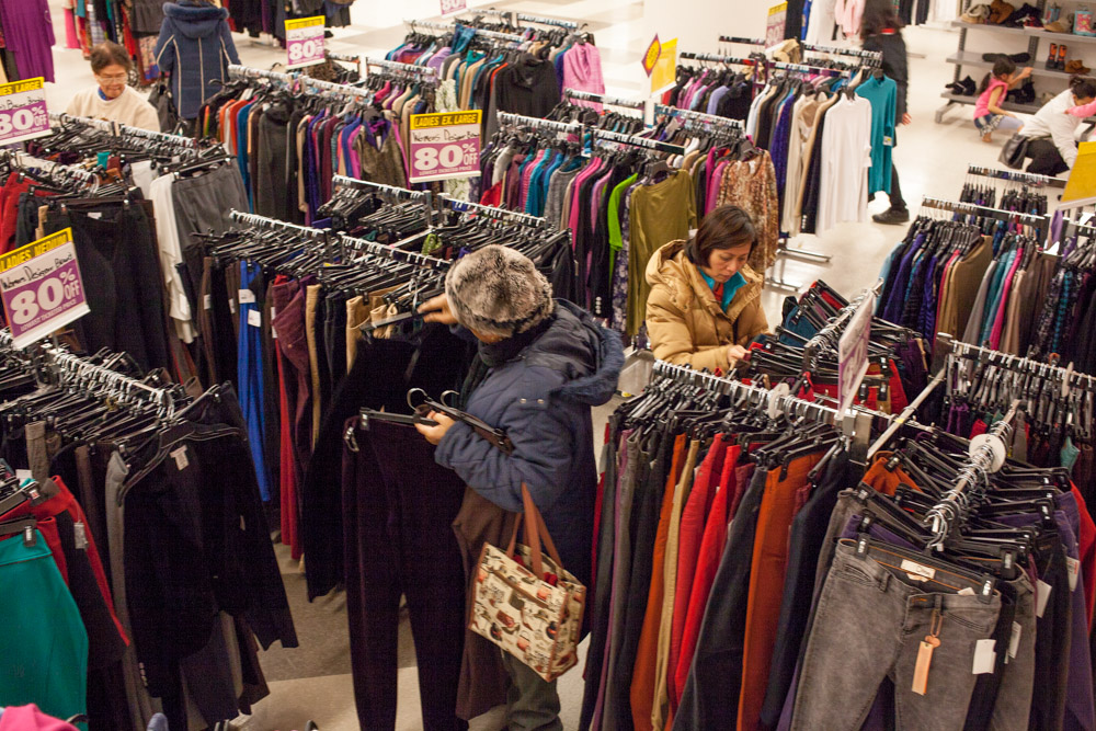 Customers rummage through heavily discounted clothing.