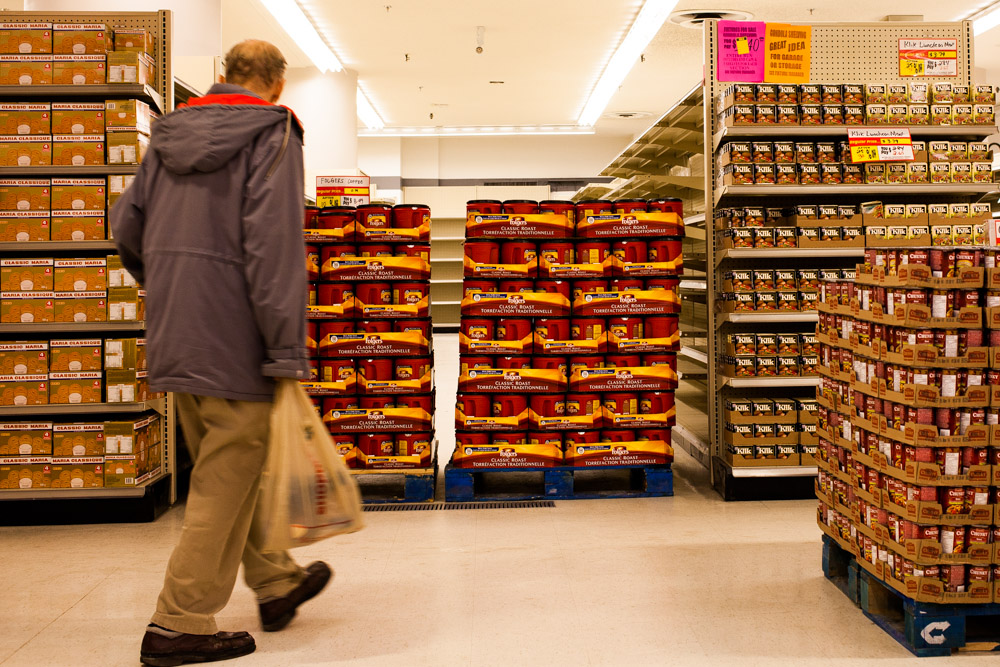 A customer wanders past pallets of cookies, coffee, canned meat, and soup.