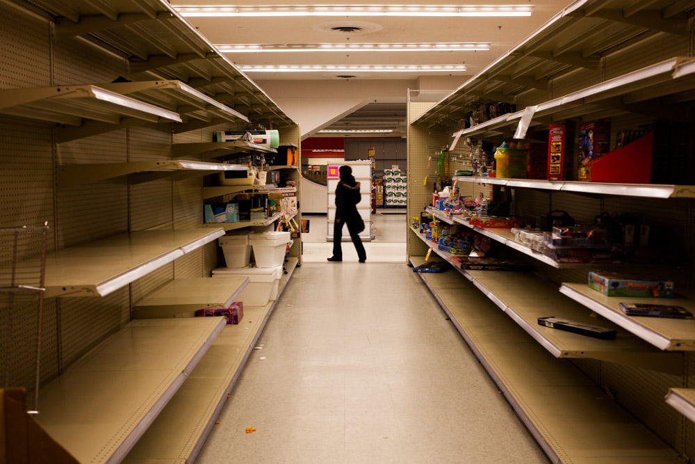 A customer wanders past an aisle that has been left with only a few items, empty packaging, and litter.