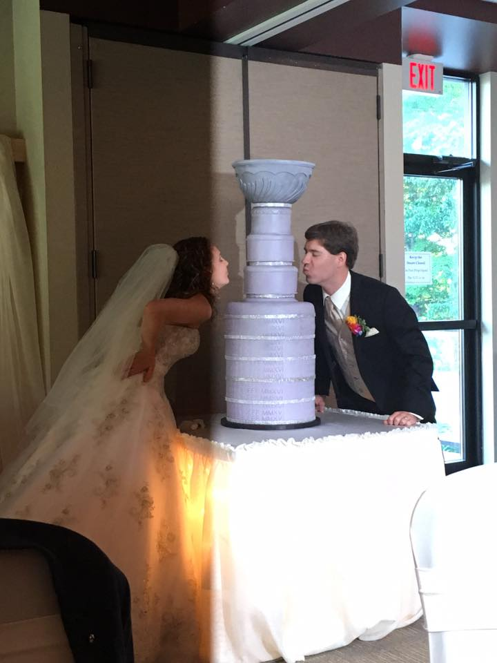 Natalie and Jeff kissing the Cup cake after their wedding win