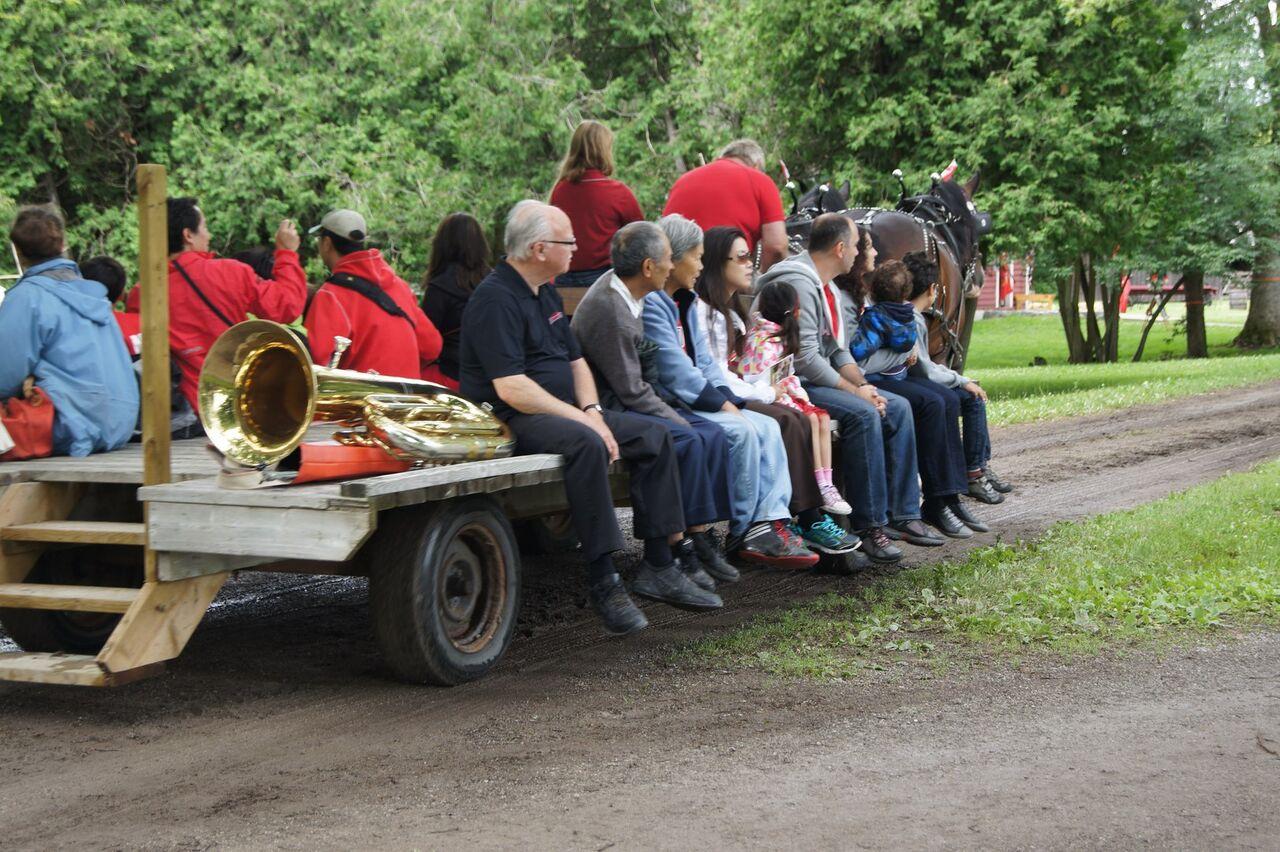 Tuba player Joe hitches a wagon ride at the 2015 Lang Pioneer Village Canada Day Celebration