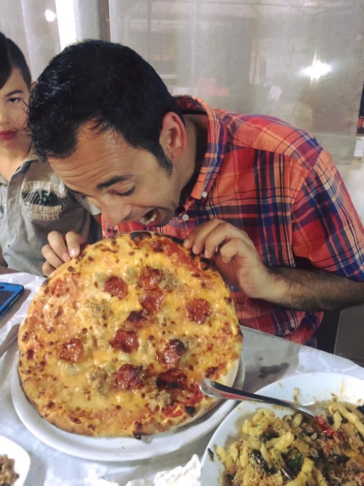 Adriano digs into a delicious pizza