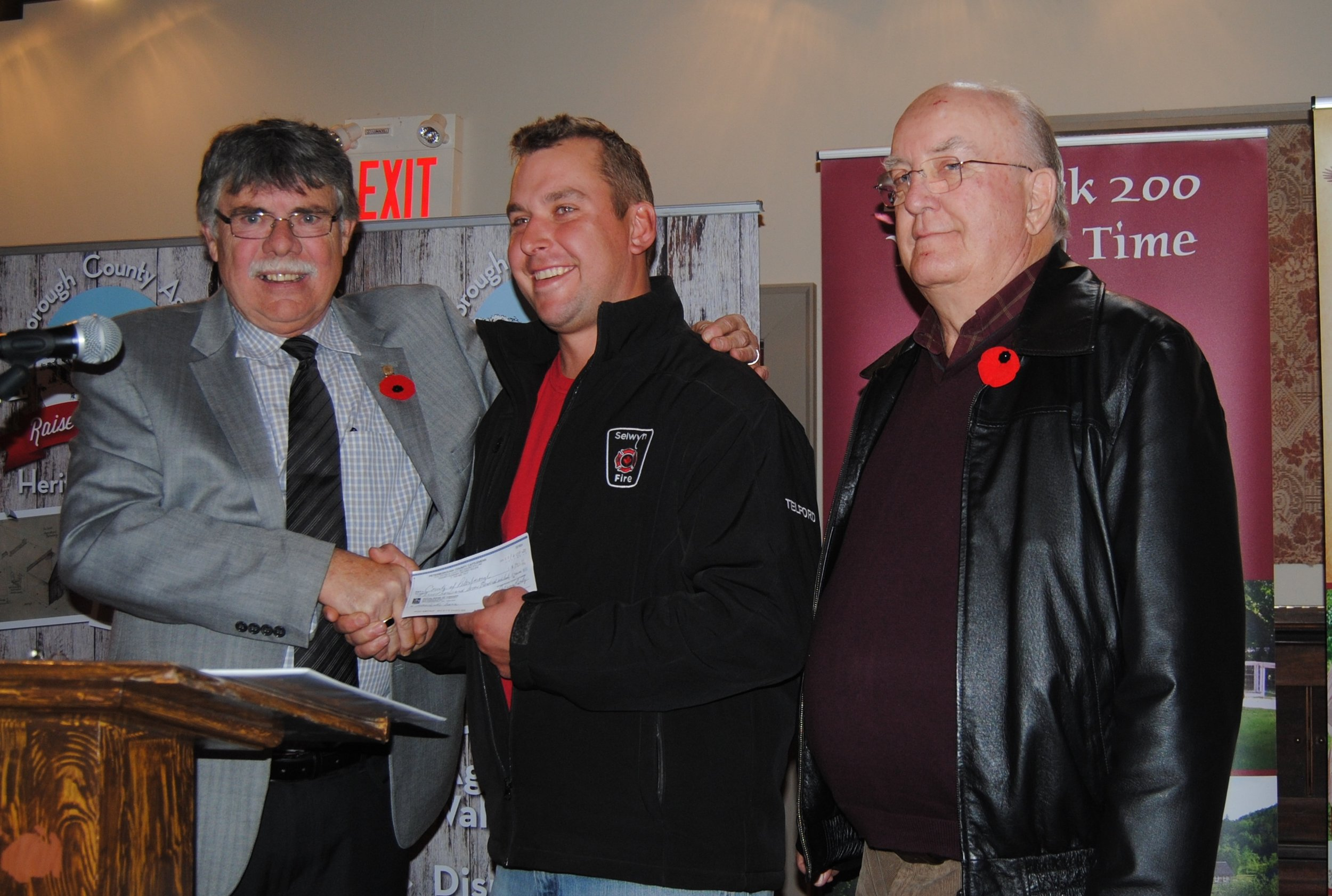 Cheque presentation of $3760 for the Peterborough County Agricultural Raising the Barn: Heritage Building.  Left to right:  Peterborough County Warden, J. Murray Jones; Mike Telford, Cattlemen's BBQ Fundraising Chair; and Larry Jinkerson, Peterborough County Cattlemen President