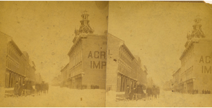 Stereopticon view of George Street looking north from Charlotte Street, c. 1880s (note that the Market Hall has not yet been built). The grand building on the right is the Bradburn Opera, which was opened in 1875. This is showing a team of horses pulling a sled up the street after a snow storm. [Trent Valley Archives, Electric City Collection]