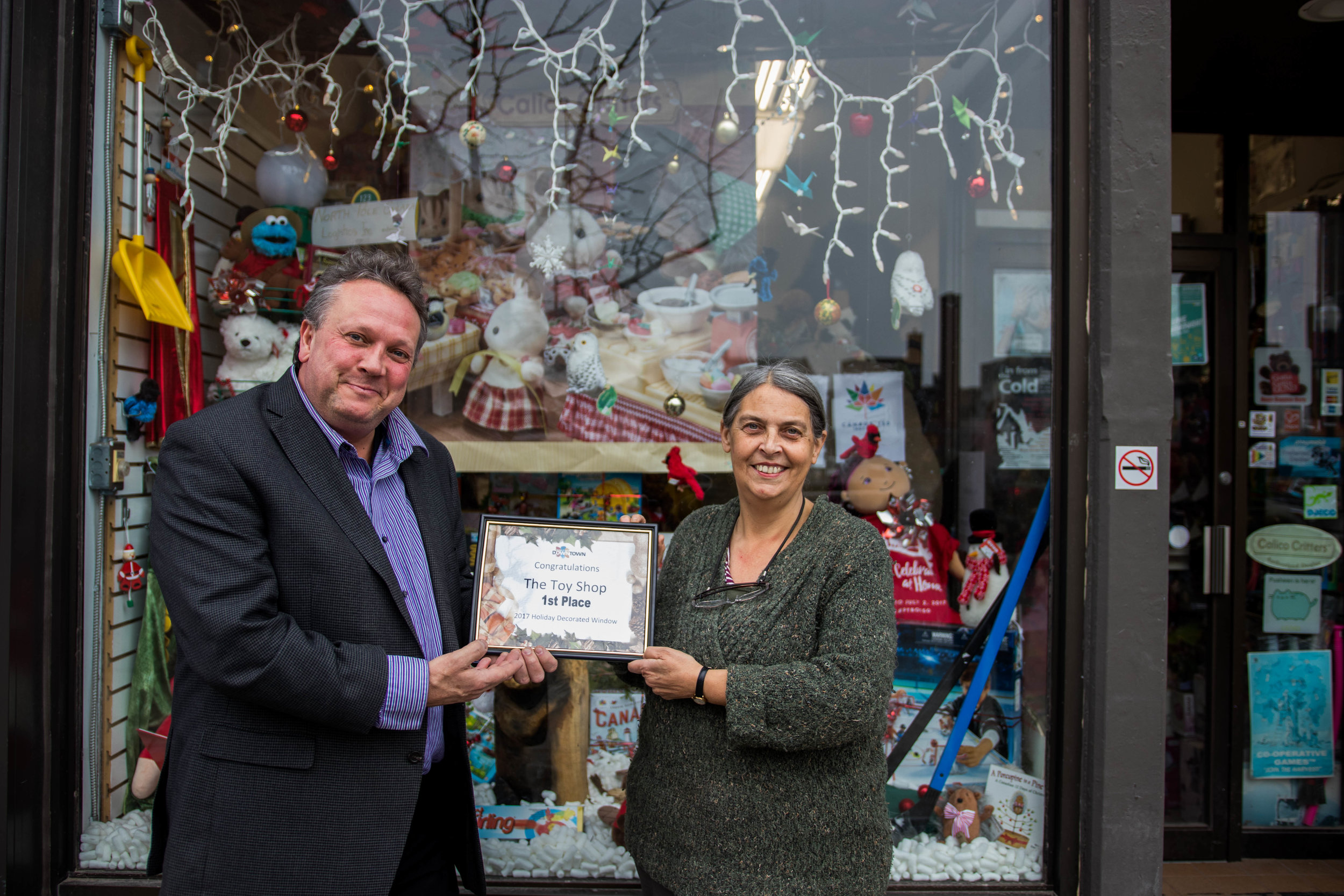 DBIA Executive Director Terry Guiel presents Toy Shop owner Jean Grant with her first place prize in the annual Holiday Window Contest.