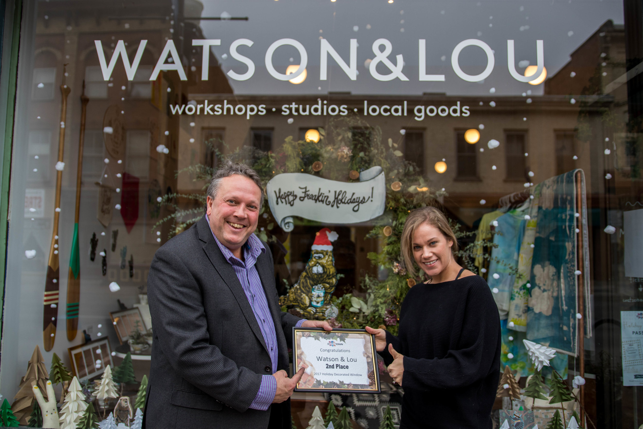 Erin Watson, co-owner of Watson & Lou, receives her second place award in the annual Holiday Window Contest from DBIA Executive Director Terry Guiel.
