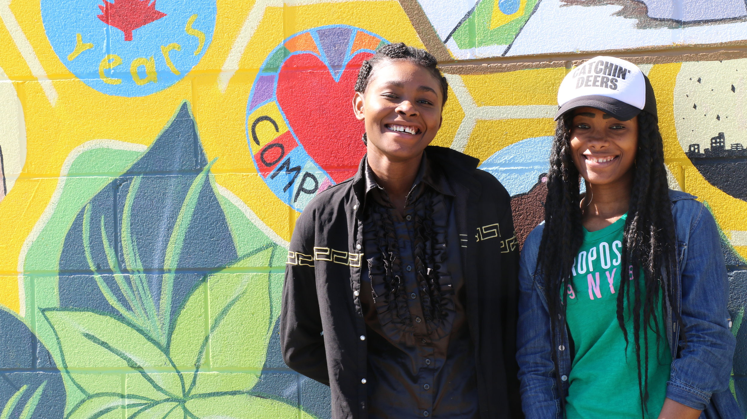 "Bintou Cherif (l) with sister Aicha in front of the ""Be Alive in Peterborough"" community mural"