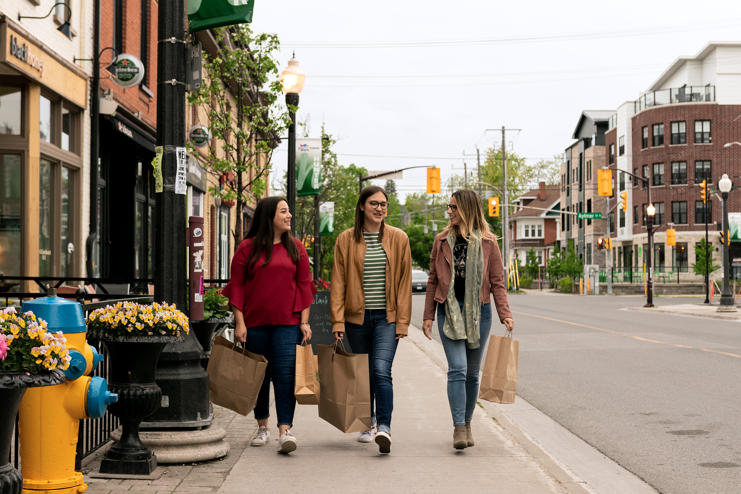 (Left to right) Aldana Casado, Kate Storen, and Chelsea Boyd pose for the launch of Open Late 'Til Eight, a new shopping initiative in Downtown Peterborough.