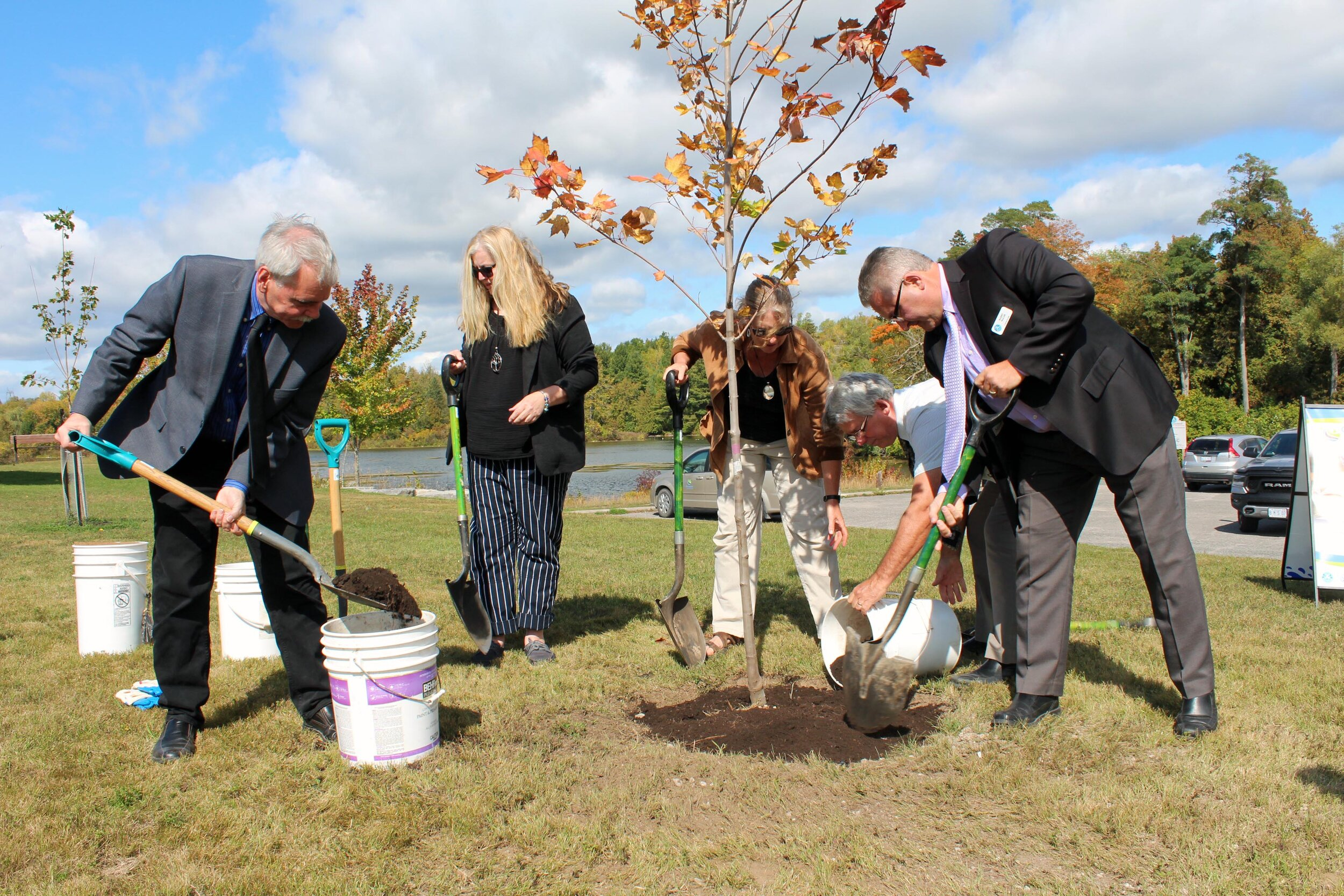 Otonabee Conservation Board of Directors Chair, Andy Mitchell (left) shovels soil around a Northwood Red Maple tree, along with (left to right) Councillor Paula Warr, Deputy Mayor Lori Burtt, Mayor Roger Bonneau, and Councillor Barry Walsh, from Township of Asphodel-Norwood in Asphodel-Norwood. (photo courtesy otonabee conservation)