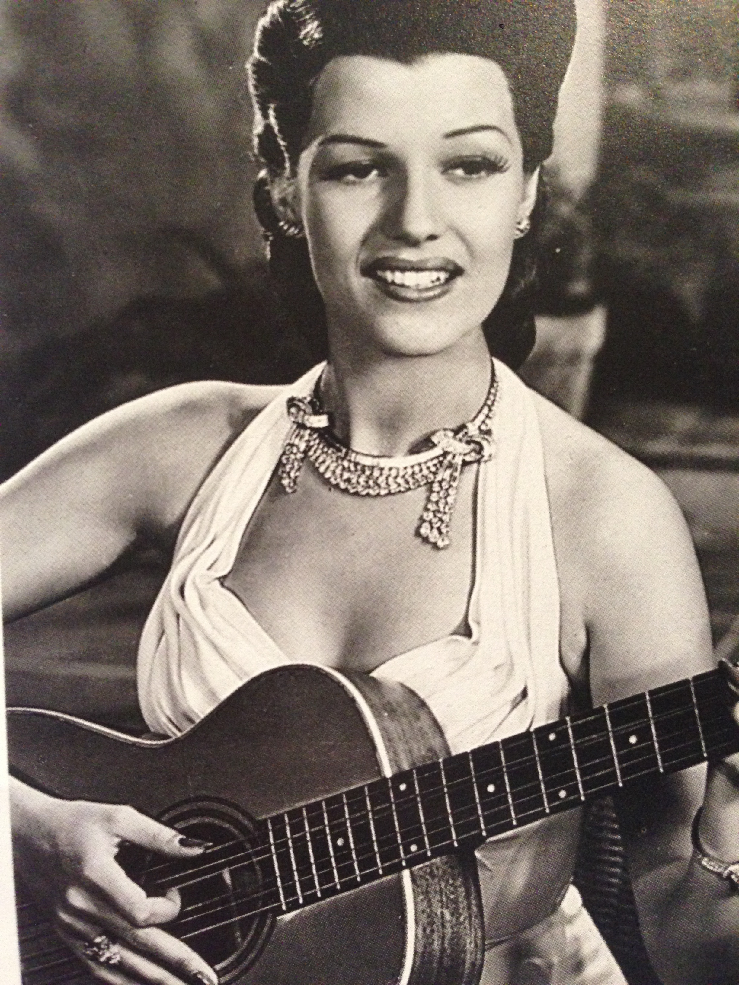 Rita Hayworth, the quintessential star:  sings, dances acts and plays the guitar.  She wears an 18k white gold and diamond swag necklace by Paul Flato.
