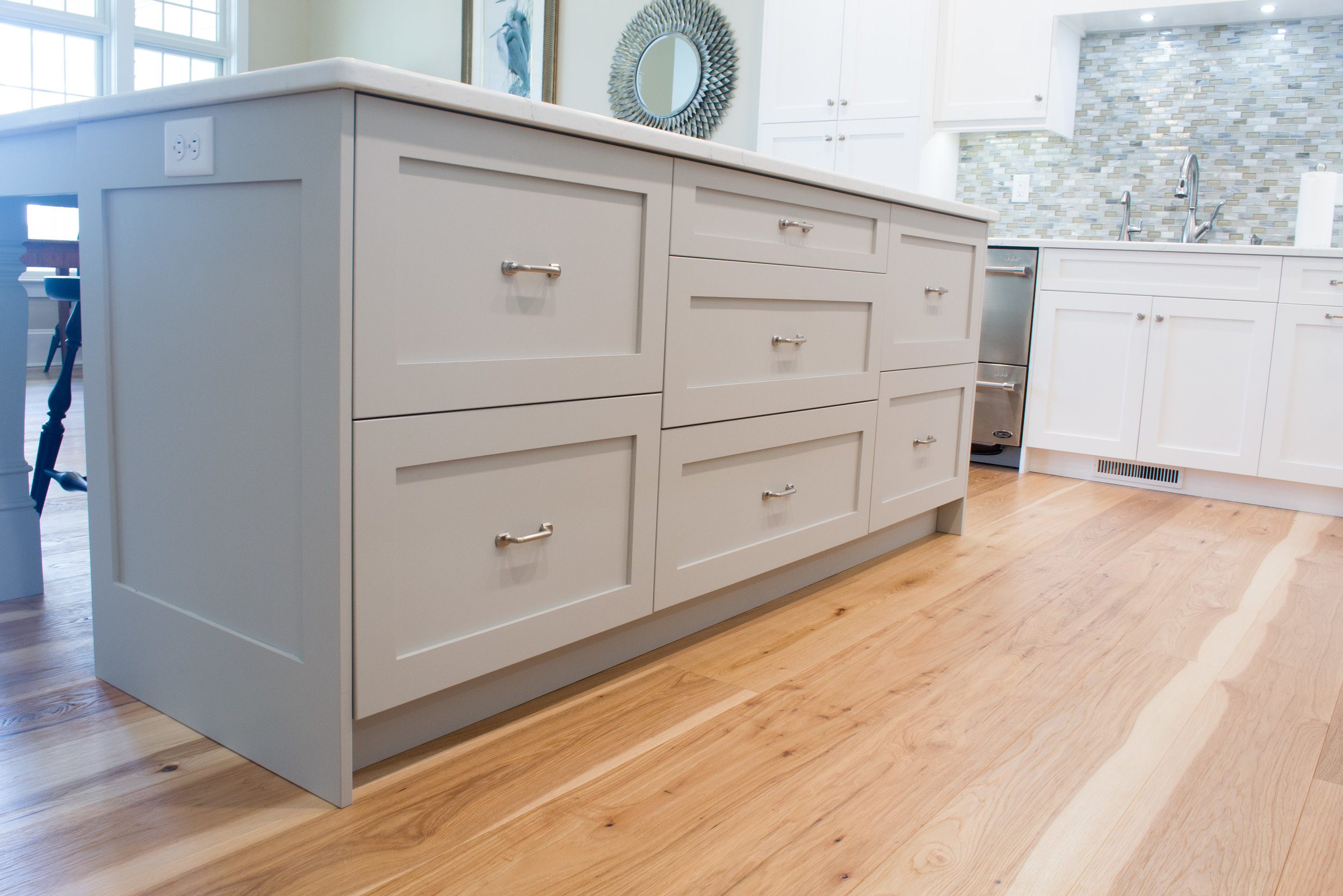 White painted kitchen with a grey island deep drawers and hidden organization