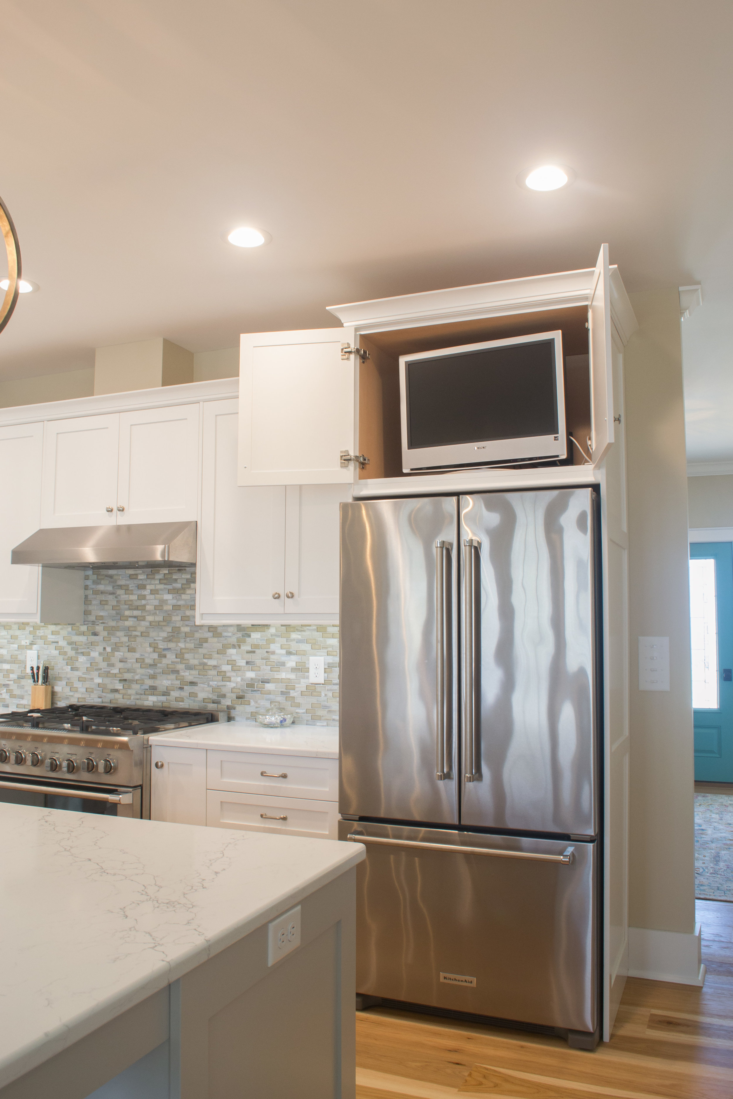 White painted kitchen with a hidden t.v. cabinet