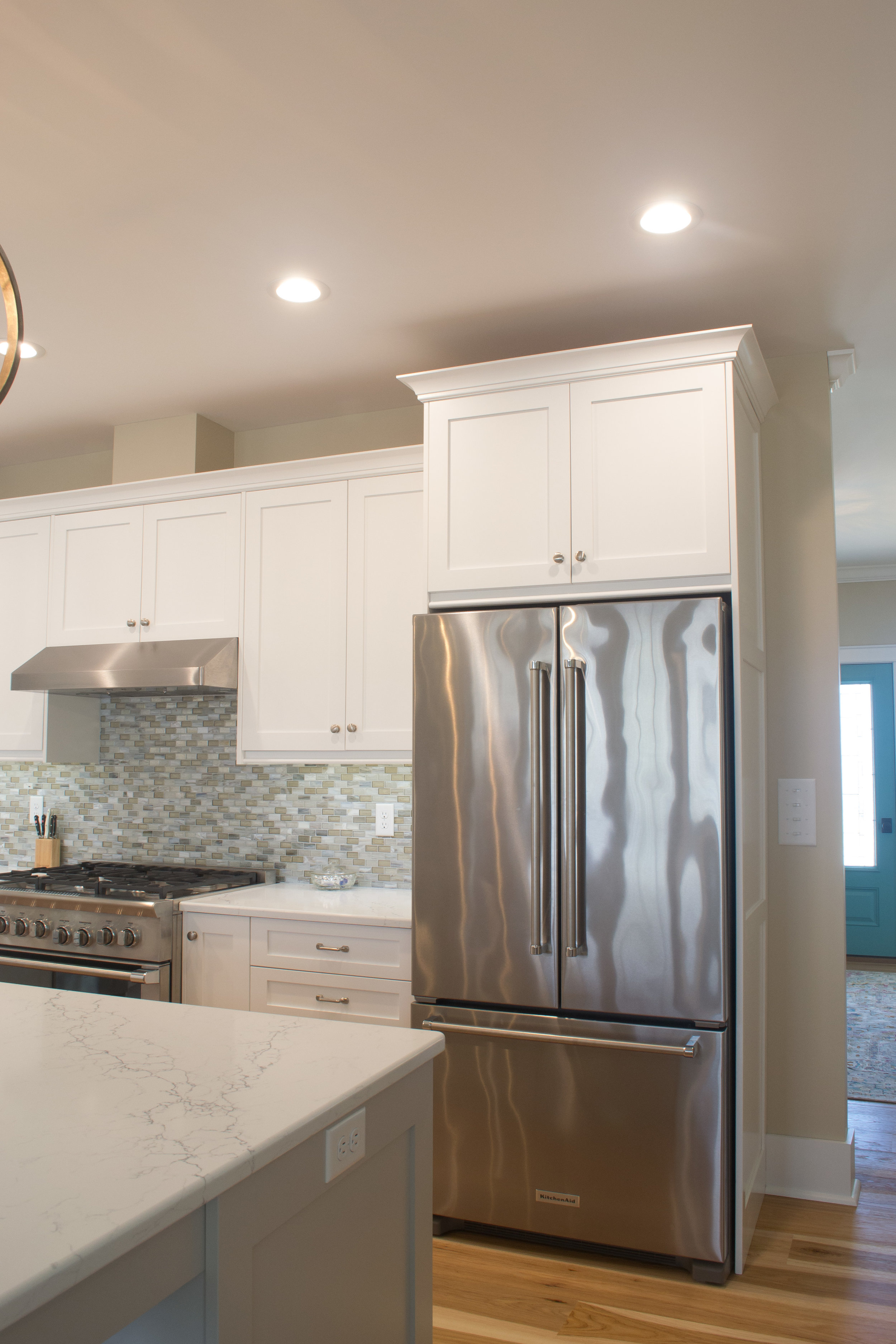 White painted kitchen with a cabinet for a hidden t.v.
