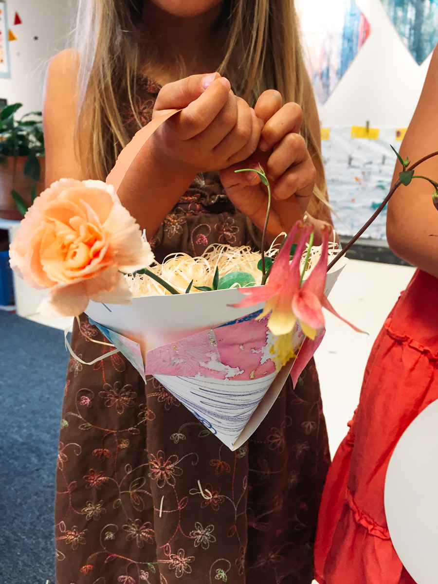 This little girls pasted painted papers to her may basket.