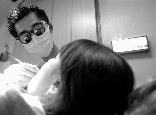 "Dr Leo Toureno working on an underserved dental patient at St Elizabeth Health Center in 2004. And yes, I still have ""spiky"" hair today. AZ Daily Star, April 18, 2004."