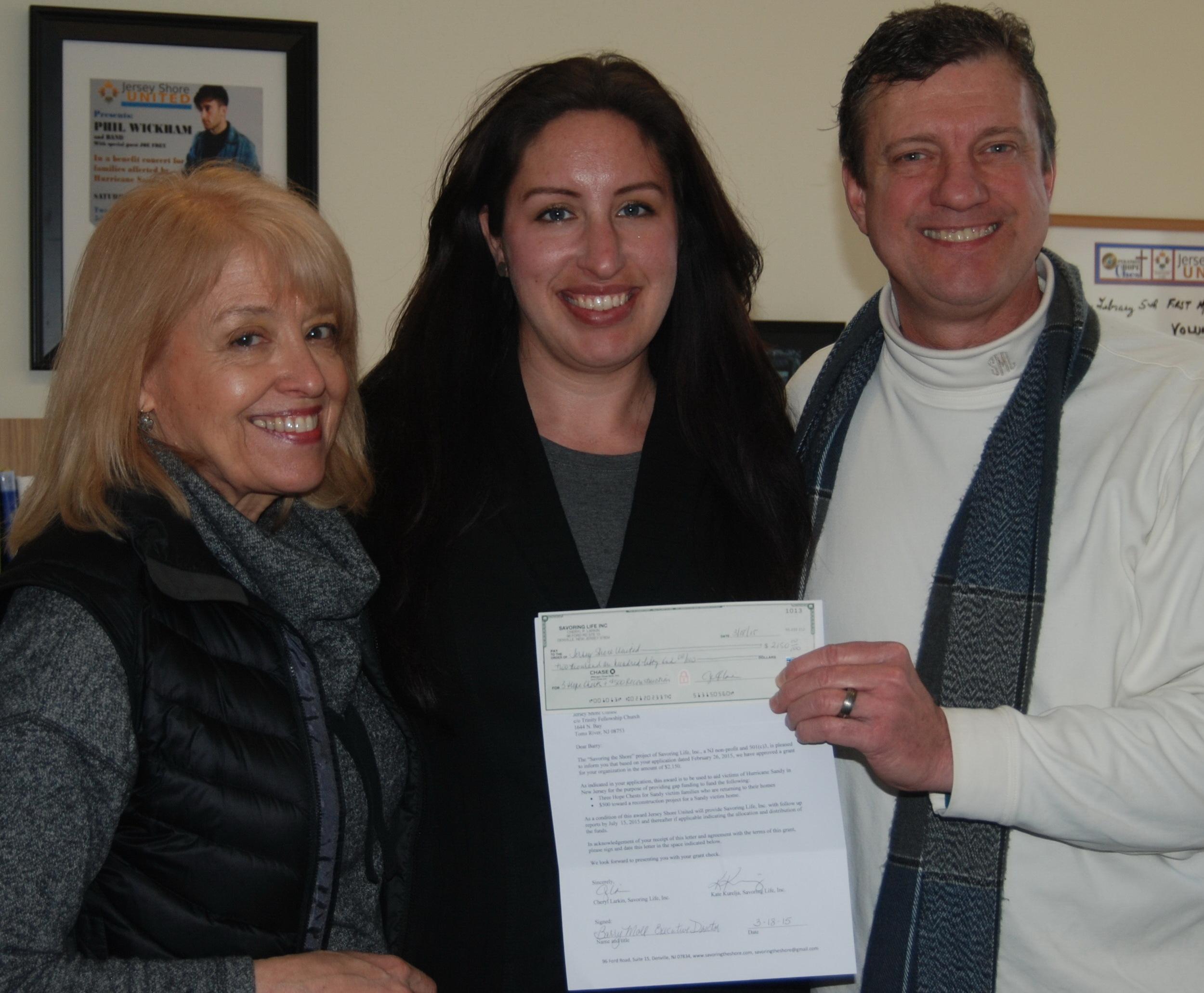 Cheryl Larkin (left) and Kate Kurelja present a Savoring grant to Barry Moll of Jersey Shore United.