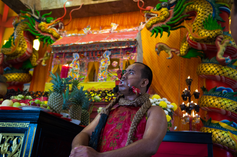 "A man in trance at a Chinese temple in Phuket during the annual vegetarian festival. The chosen spirit mediums or ""mah songs"" are the devotees through which the gods communicate. They often self-mutilate their bodies in order to absorb evil spirits and bring good luck to the community."