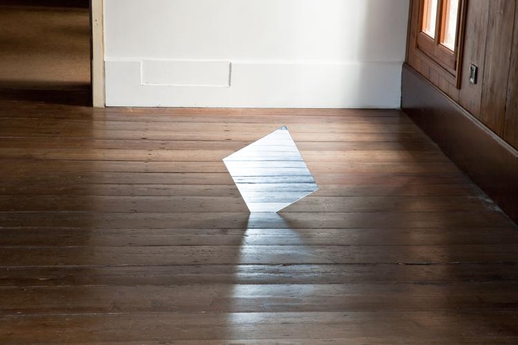 Alex Perweiler  Mirror Drop  2012  Mirror inserted into floor  12 x 12 x 1/4 inches