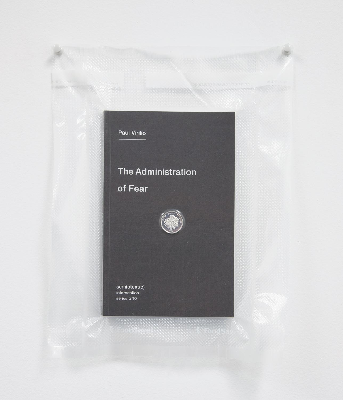 Brad Troemel   TSA No Fly List Vacuum Sealed Paul Virilio     -'The Administration of Fear' with AOCS Solid Silver Prosperity Treet coin  , 2013   10 x 8 inches