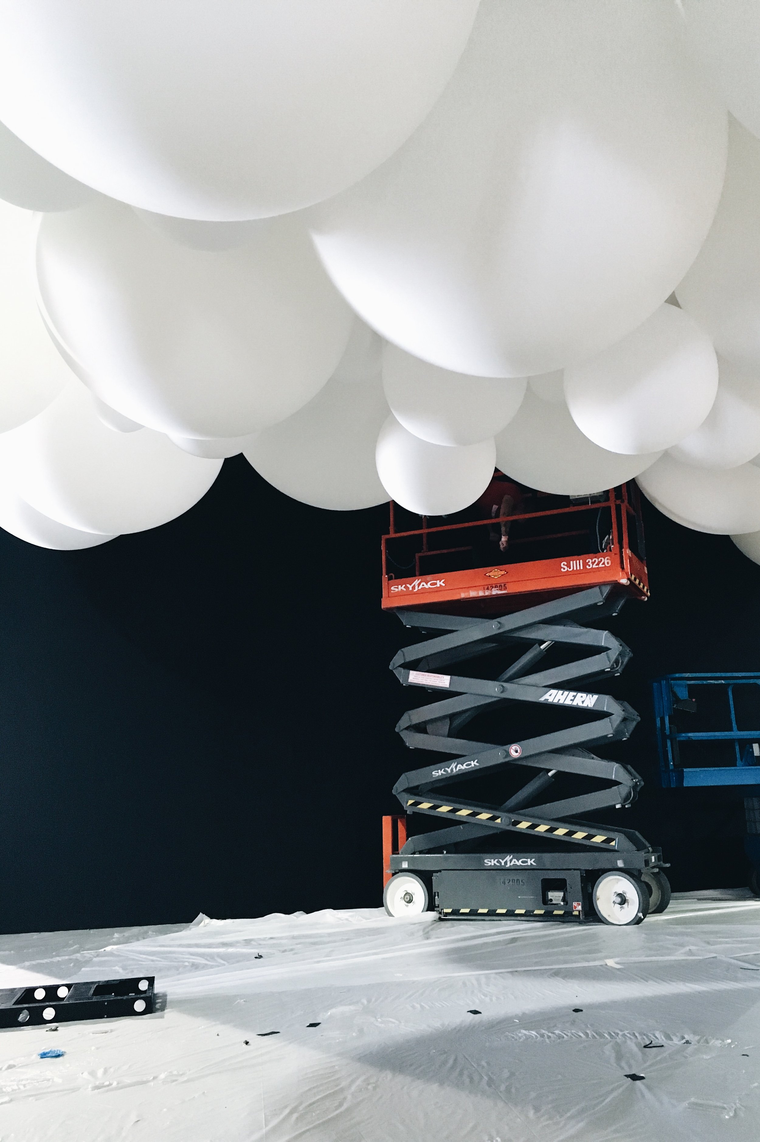 Riggers on the scissor lift filling in balloons after the truss was brought to trim height.