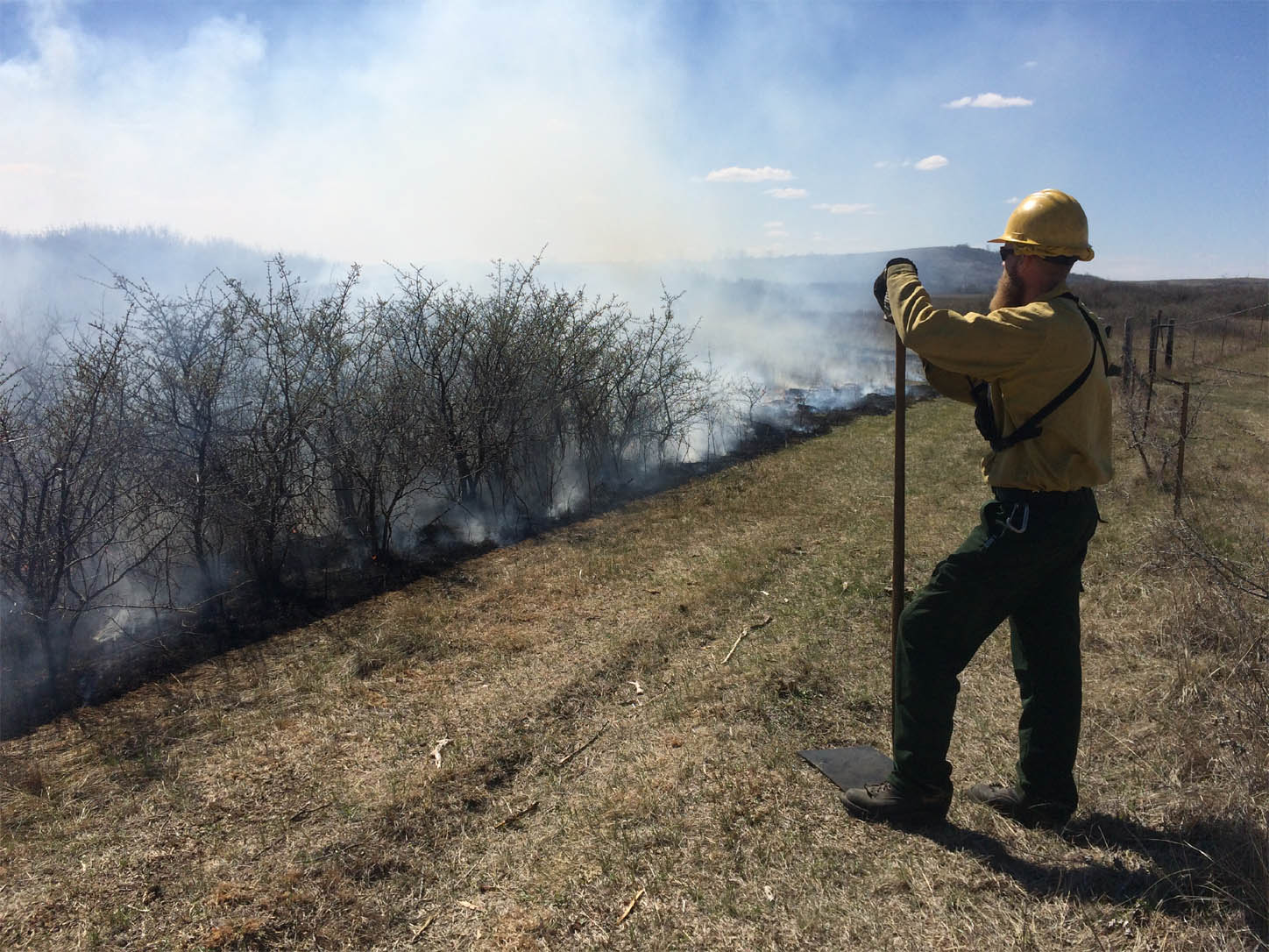 Alan Teed, a Burn Crew Member, monitors a prescribed fire...