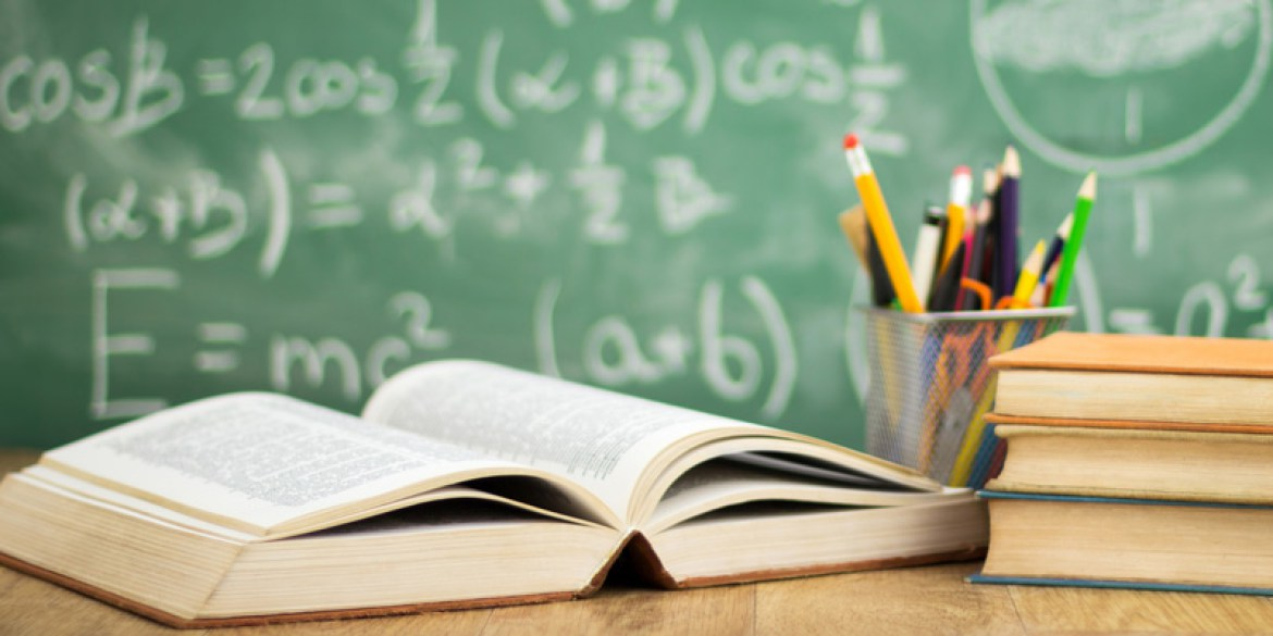 [feature image shows open textbook in foreground and pencils. In background is blurred chalkboard  via ]