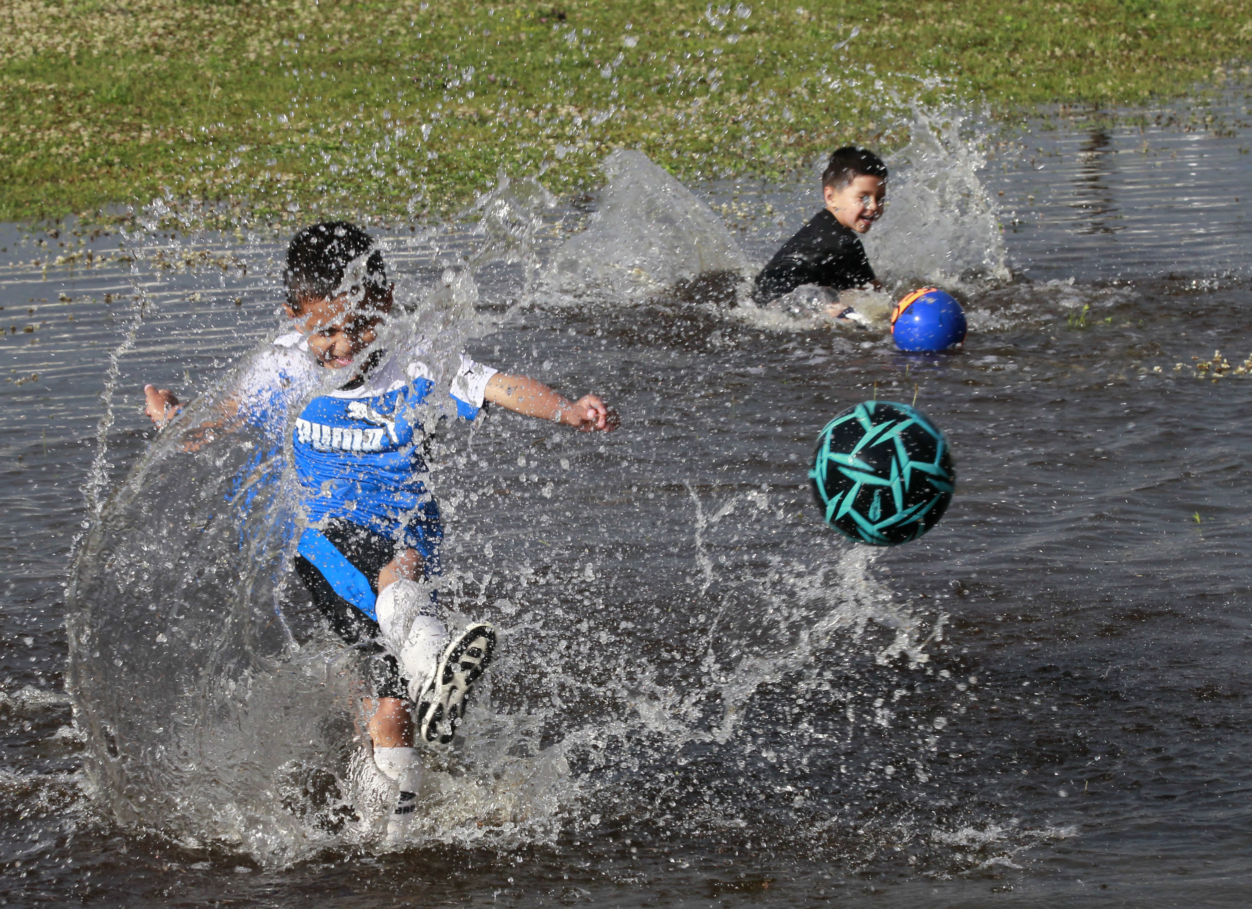 Toledoans Diego Mosqueda, 7, and his brother Tavio Mosqueda, 4, play soccer in the flooded front yard of DeVeaux Elementary School in Toledo, Ohio. Twenty minutes of a steady downpour created a small pond big enough to attract the young athletes.  ©2014/Toledo Blade/Lori King
