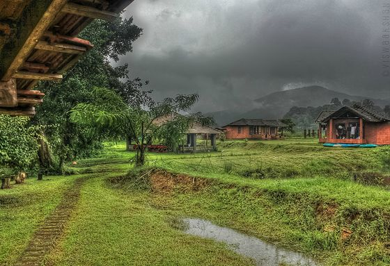 Dark clouds over small huts and hills