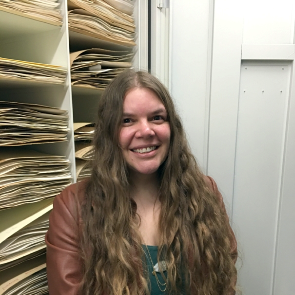AJ standing in front a cabinet of dried, pressed plant specimens at the National Museum of Natural History of the United States.