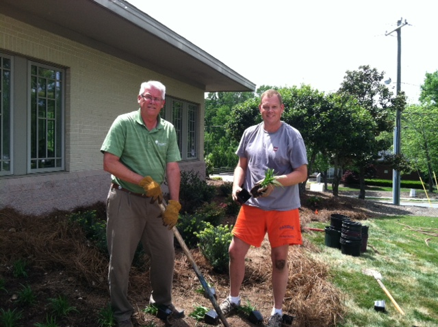 Gary Upchurch from New Garden Landscaping & Nursery works with a volunteer to plant the memorial garden.