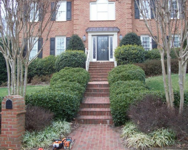 Before renovation. Shrubs are beginning to lose definition and grow into the walkway and over the windows.
