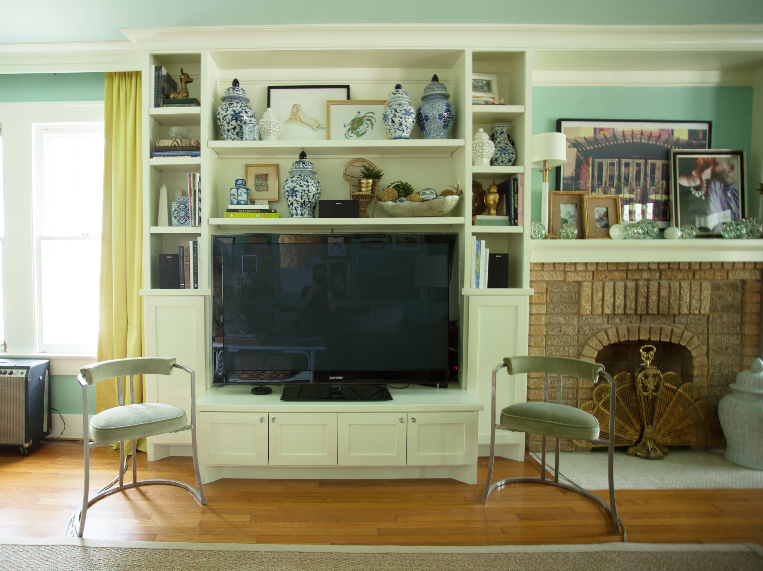 Built-in TV cabinet around fireplace in living room in a 1920s Houston Heights bungalow by Jamie House Design. Updated historic bungalow.