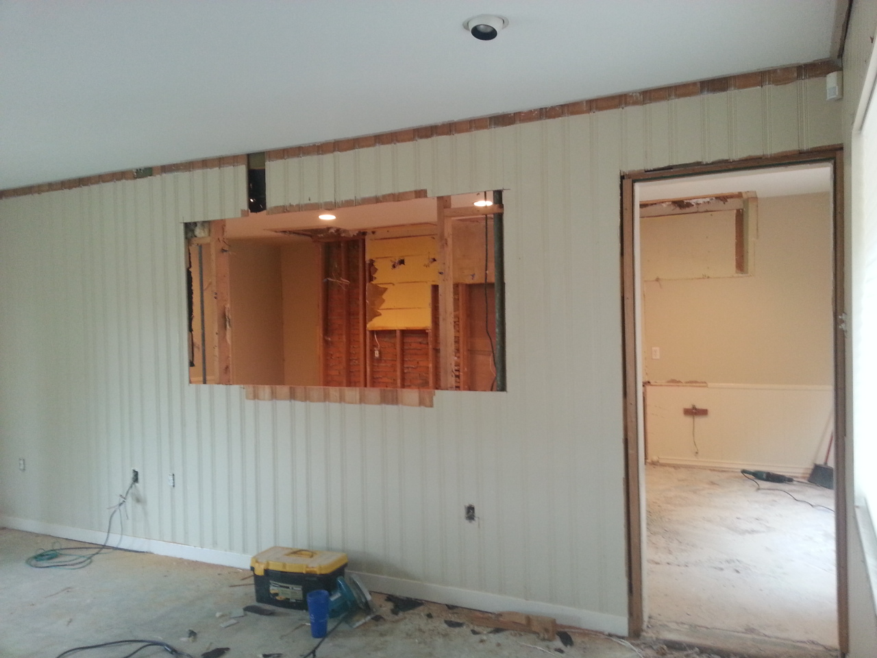 DURING. In widening the kitchen peek through we realized that there is NO drywall behind that paneling. You can see the backside of the fireplace next to the original pantry also.