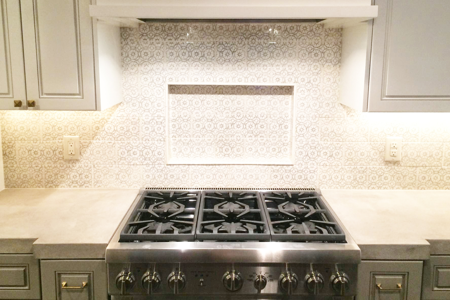 Pratt and Larson tiles on backsplash behind range in Houston Texas kitchen remodel by Jamie House Design. Concrete counters in kitchen.