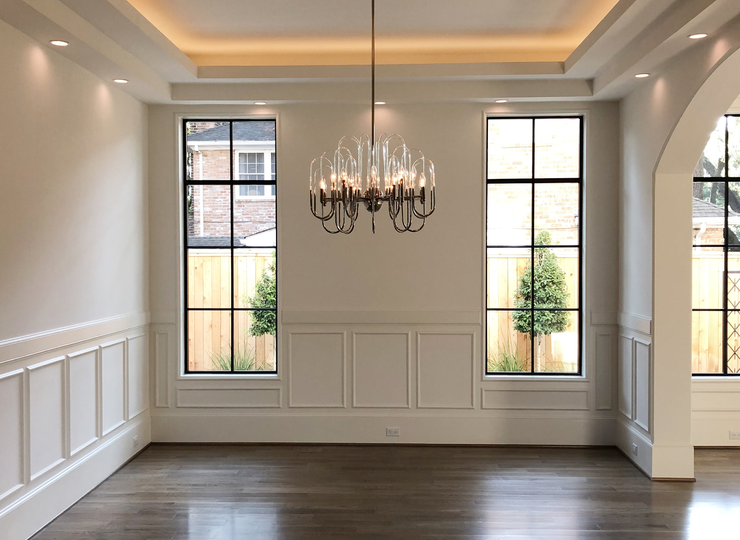 Classic moldings are highlighted by steel windows and the contemporary glass chandelier in the a dining room designed by Berlin based interior design firm Jamie House Design.