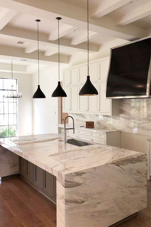 Kitchen in Houston's River Oaks neighborhood with marble waterfall island and black range hood designed by Berlin based interior design firm Jamie House Design and built by CM Batts Developers.